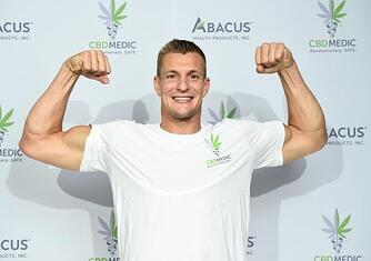 A photo of NFL star Rob Gronkowski at an event with his CBD sponsor.